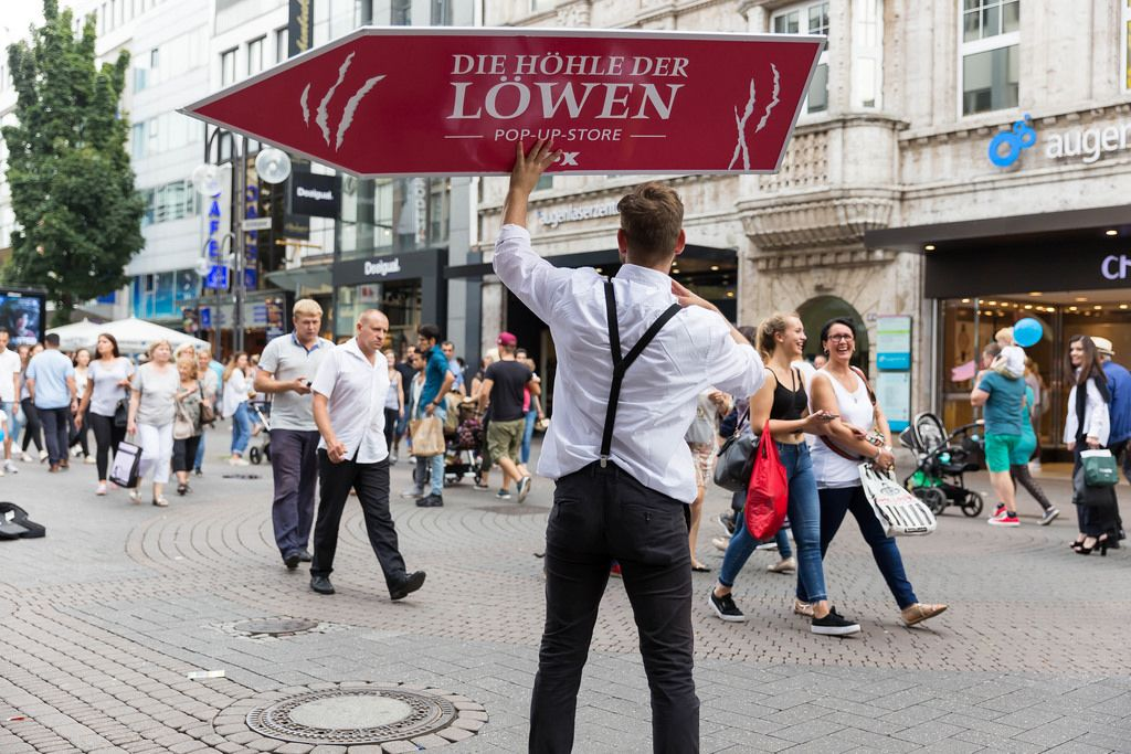 Promoter with a banner for the Pop-up-Store Die Höhle des Löwen