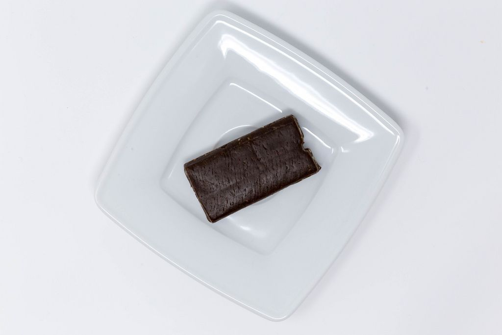 Pulsin Roher Schokoladen Brownie auf weißem Teller - Aufsicht