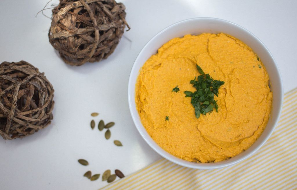 Pumpkin hummus in a bowl with parsley and punpkin seeds aside - top view