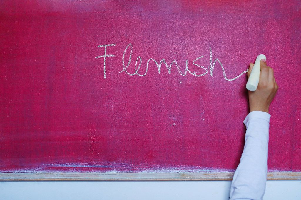 Pupil writting Flemish on chalkboard
