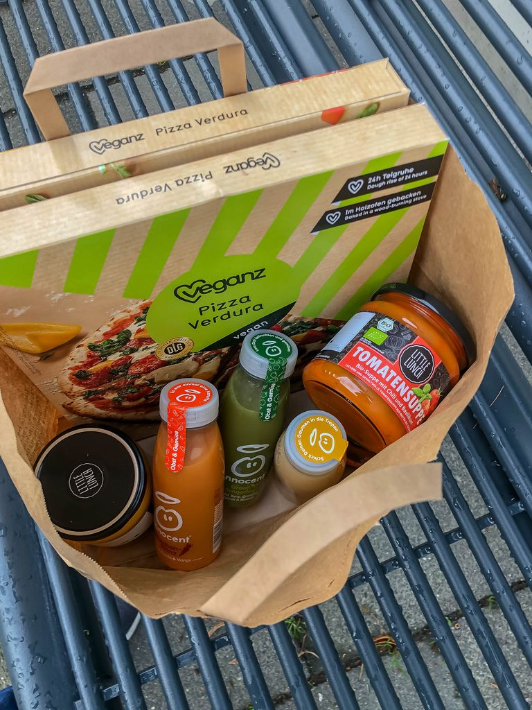 Purchasing healthy foods like tomato soup, vegan pizza and fruit juices in paper bag