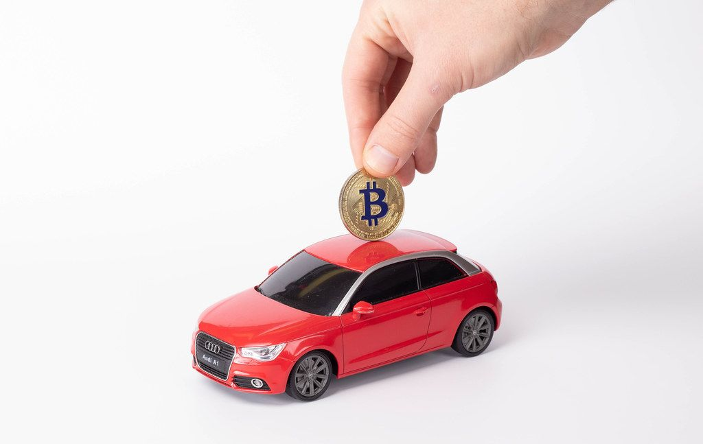 Putting Bitcoin into the car on white background
