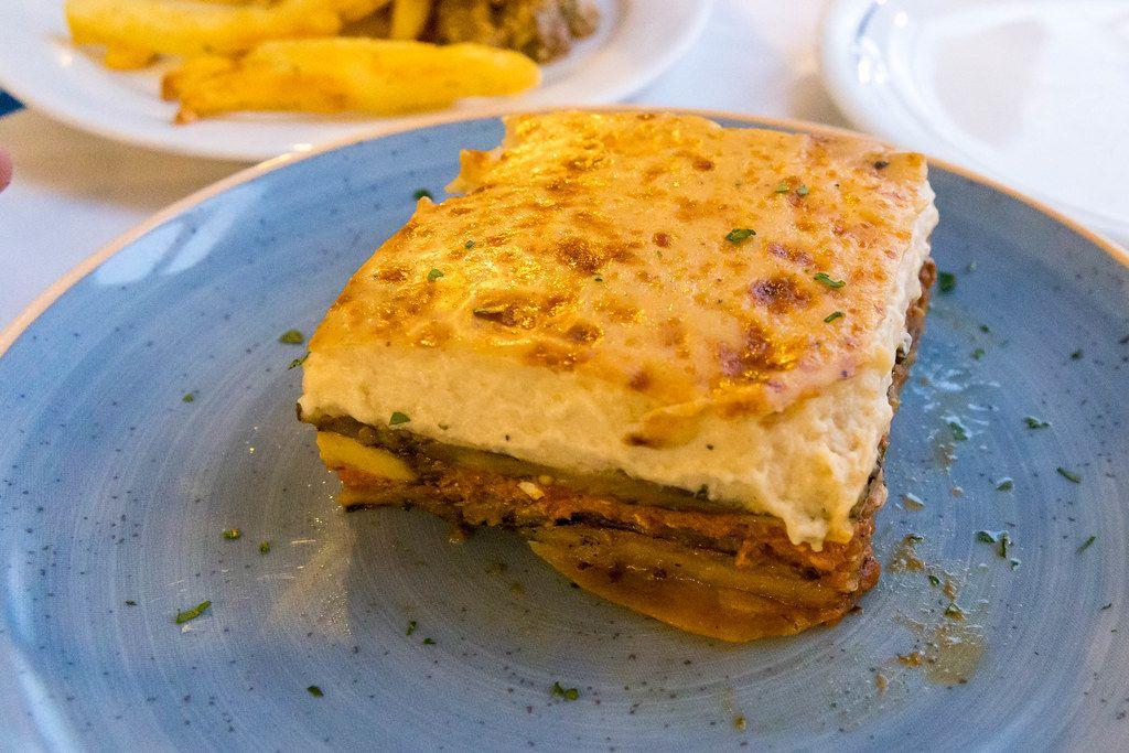 Quadratisches Stück Lasagne, auf einem blauen Teller