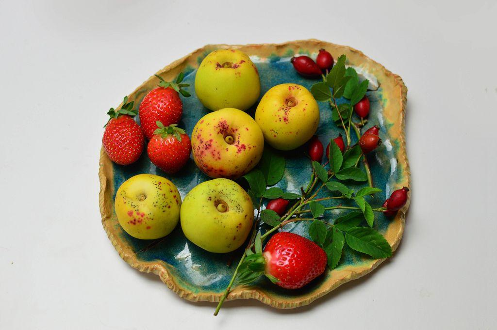 Quitten mit Erdbeeren und Hagebutten auf Obstschale