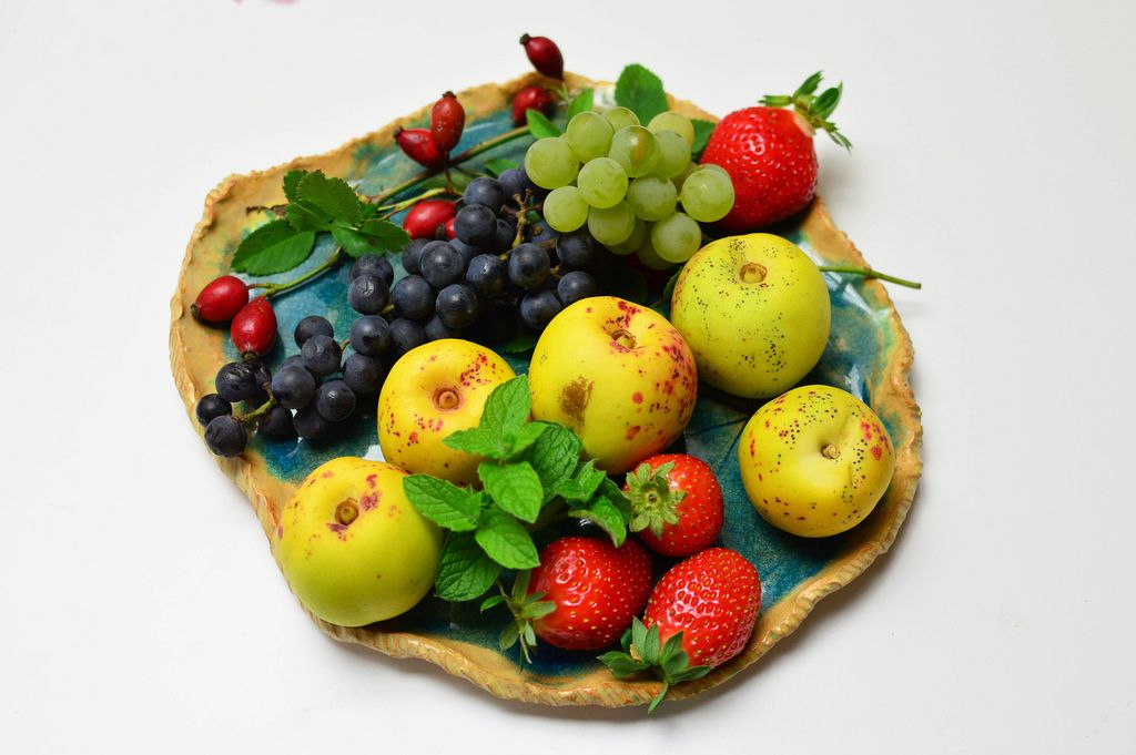 Quitten mit Weintrauben, Erdbeeren und Hagebutten auf Obstschale aus Ton