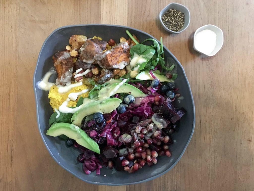 Rainbow Bowl mit Granatapfel-Kernen, Avocado, Rotkohl, Blaubeeren und Süßkartoffeln