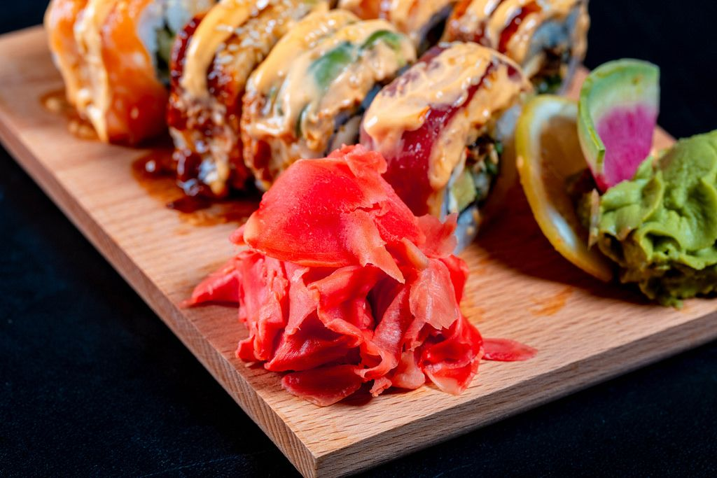 Rainbow dragon sushi set with ginger, lemon and wasabi on wooden Board