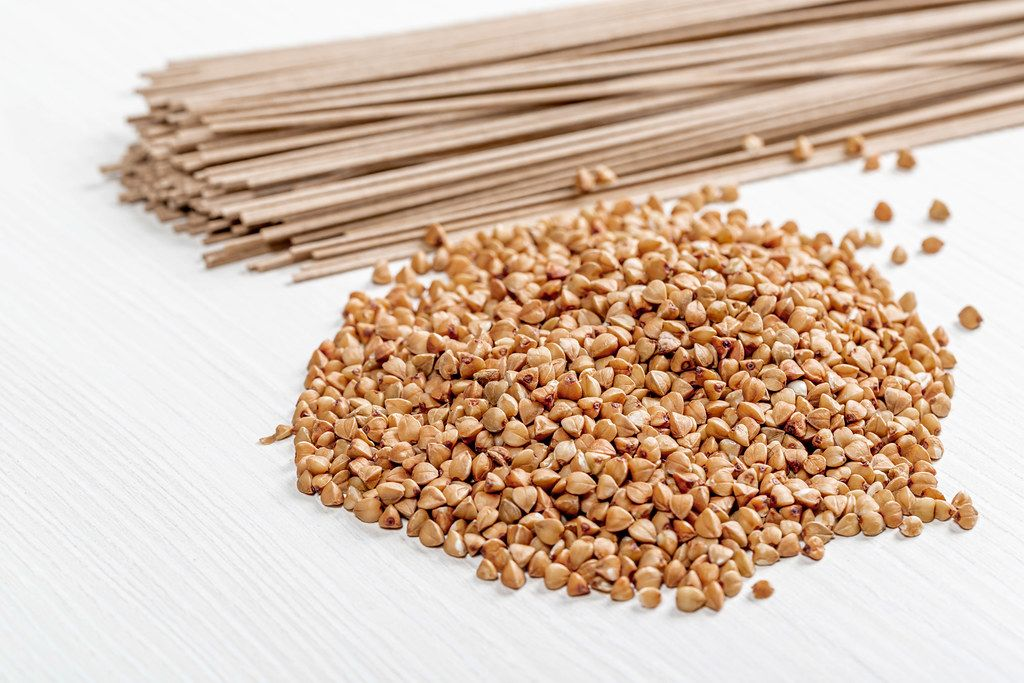 Raw buckwheat and buckwheat soba noodles on white wooden background