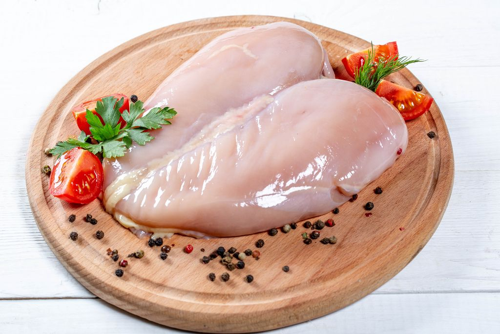 Raw chicken breast fillets with spices on the kitchen Board