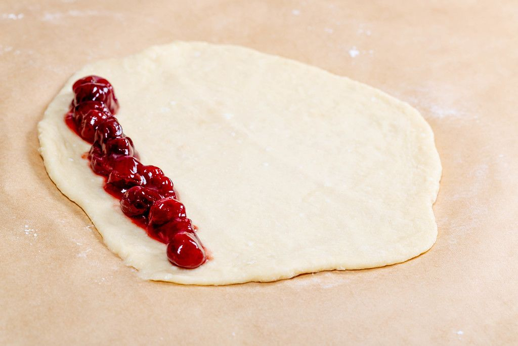 Raw dough for buns with cherry jam