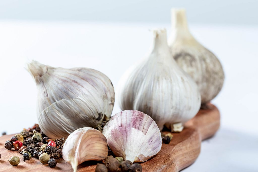 Raw garlic and black pepper on the kitchen Board