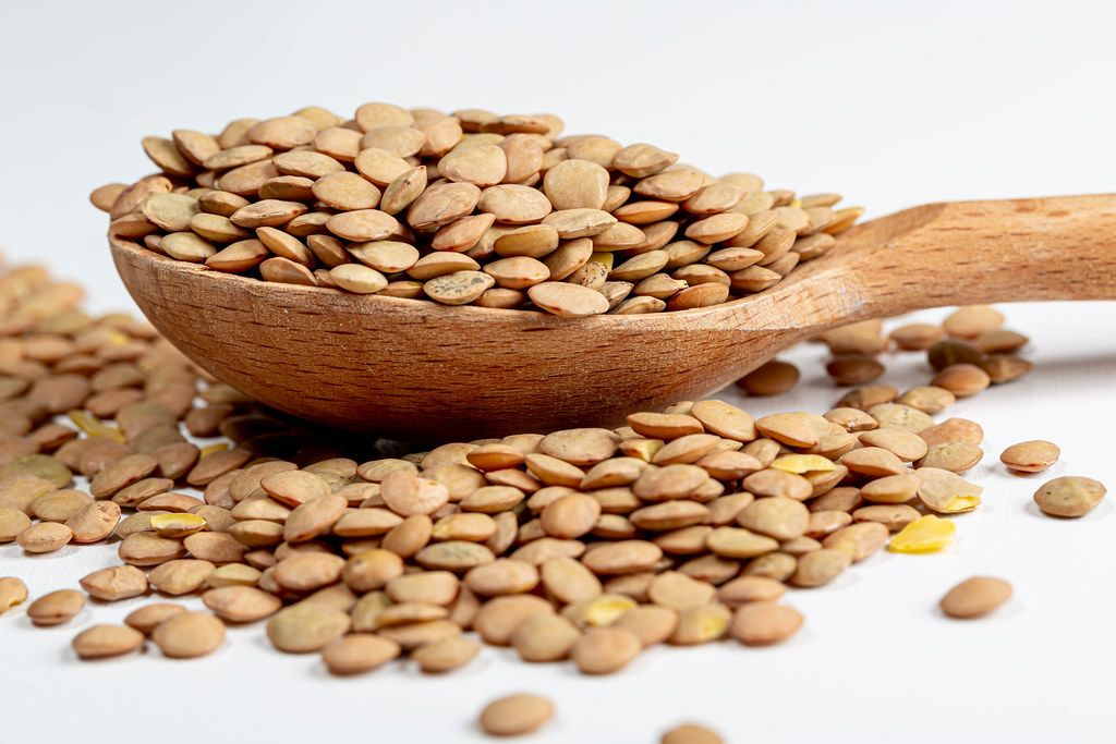 Raw pardin lentils in a wooden spoon