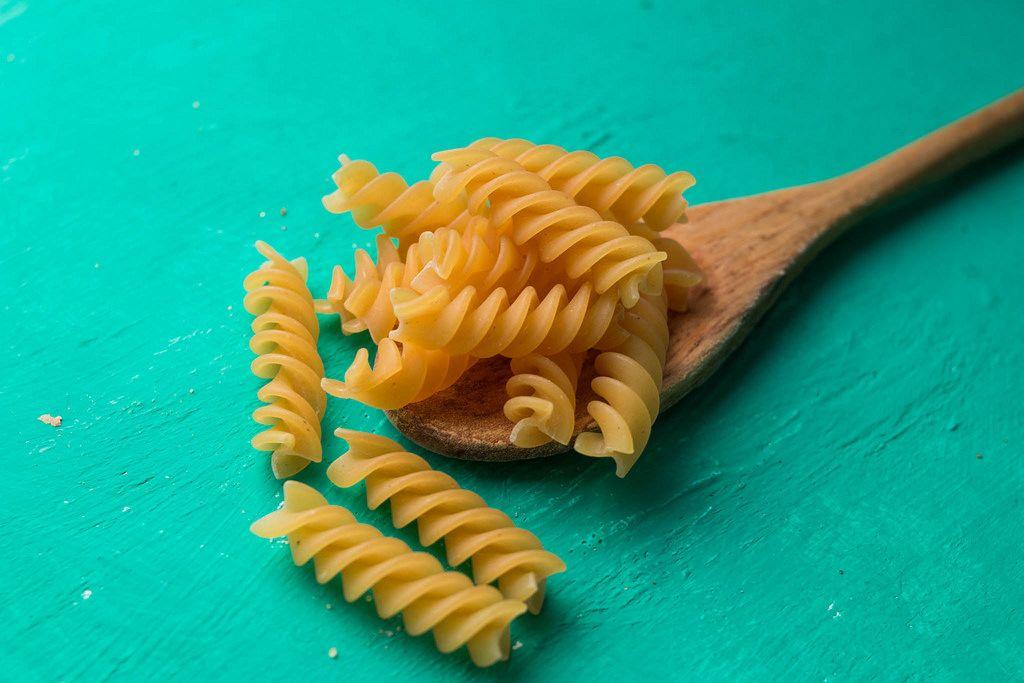Raw pasta on wooden spoon