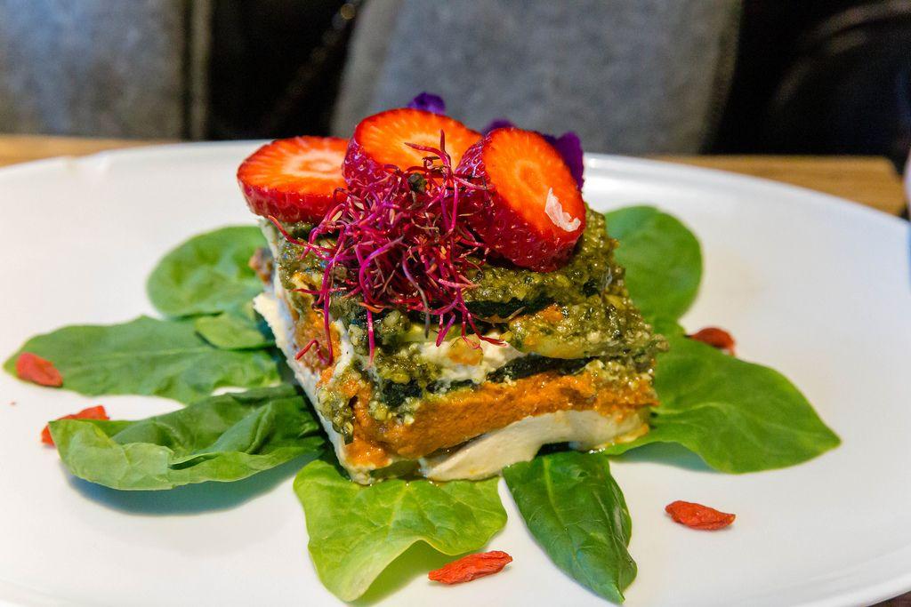 Raw vegan lasagna with raw zucchini, fresh tomatoes, baby spinach, cashews, macadamia cheese and basil pesto at Flax&Kale restaurant in Barcelona