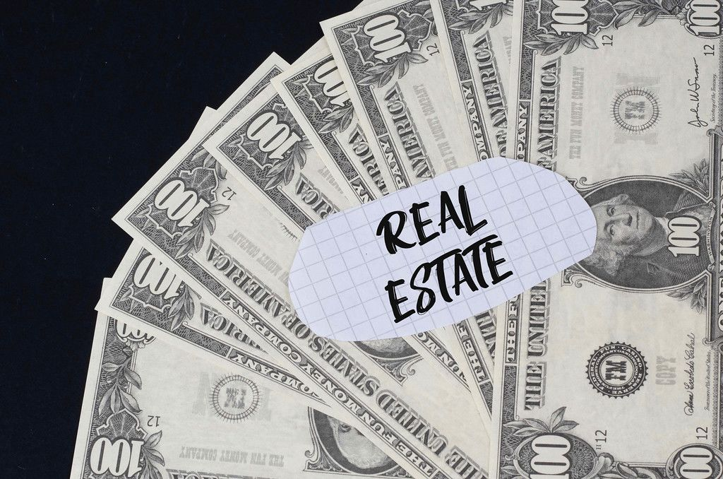 Real Estate text and dollar banknotes