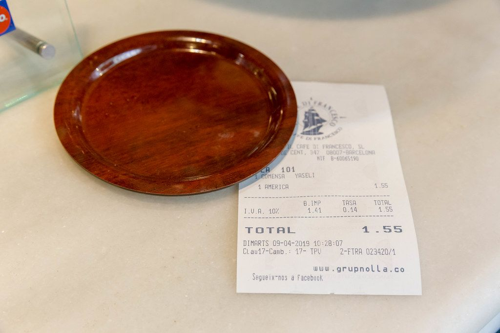 Rechnung aus einem spanischen Café in Barcelona, unter eine braune Untertasse geklemmt