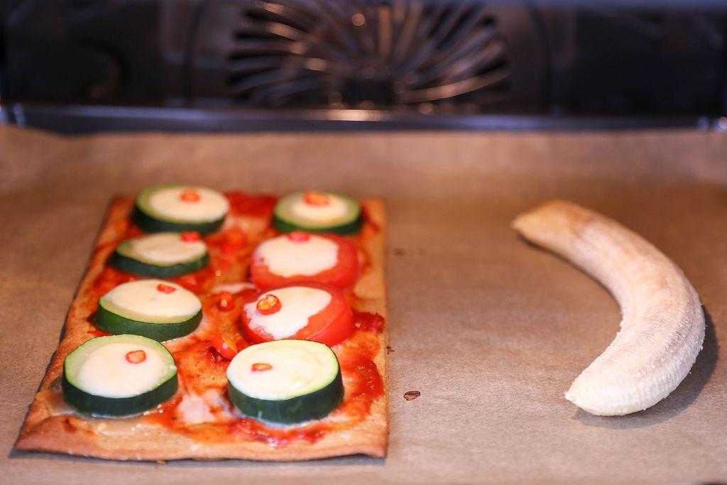 rechteckiges Pizzastück mit Zucchini- und Tomatenscheiben, überbacken mit Käse im Backofen neben einer geschälten Banane