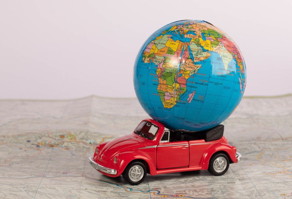 Red beetle car with globe on map