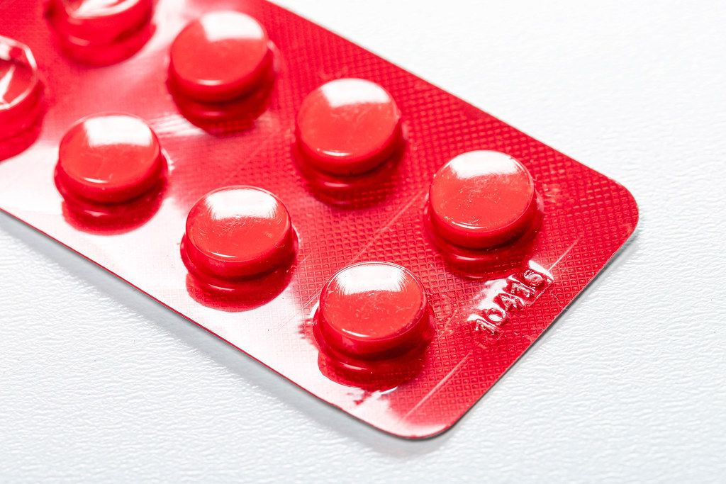 Red blister with pills on a white background (Flip 2019)