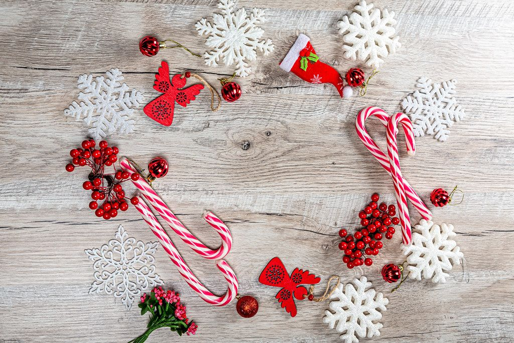 Red Christmas decor and white snowflakes on wooden background with free space