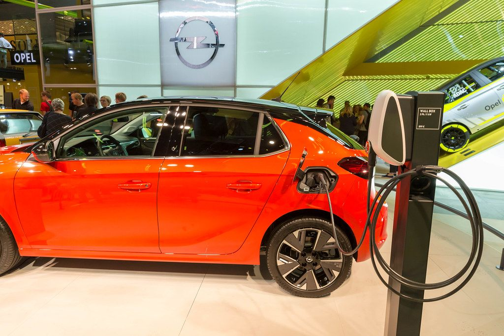 Red electric vehicle by Opel: Corsa-e The charges with universal cable at a Wall Box charging station