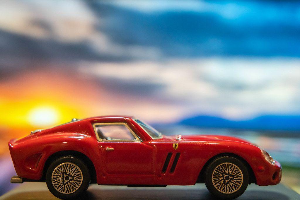 Red Ferrari toy car on platform with sunset background (Flip 2019)