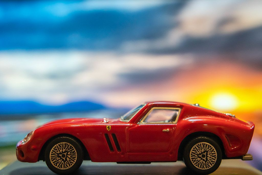 Red Ferrari toy car on platform with sunset background