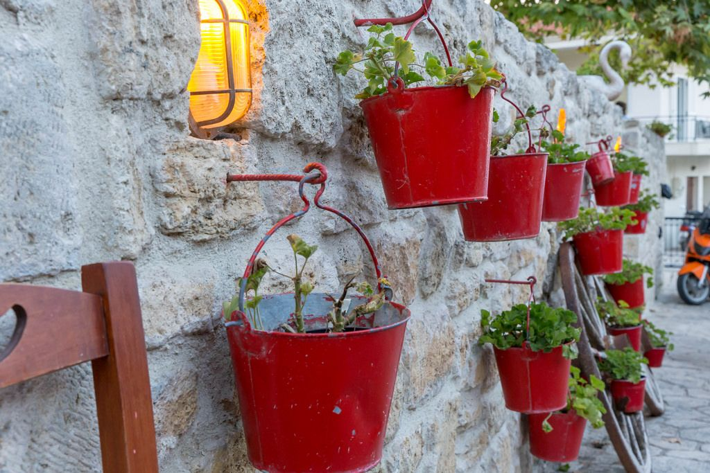 Red flower buckets hanging on hooks on a wall