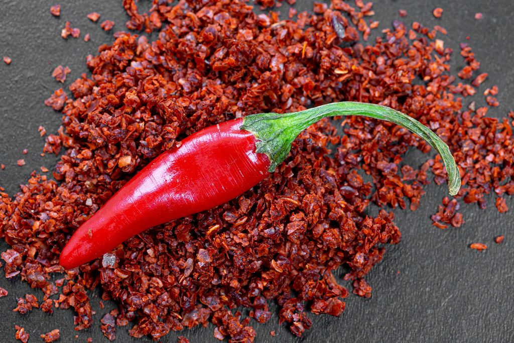 Red fresh chili pepper and dry ground hot pepper on black background