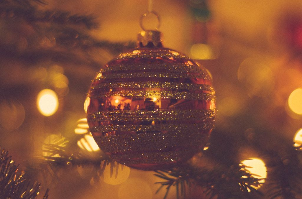 Red-golden christmas tree ball with branches and festive lights in the background
