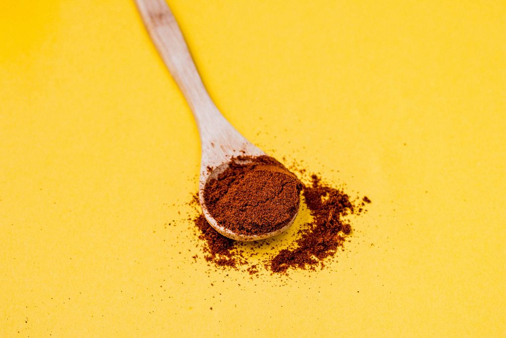 Red pepper spice on wooden spoon. Yellow background