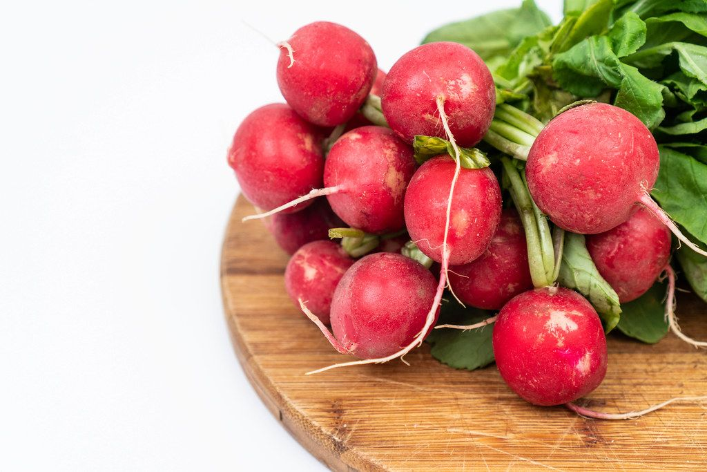 Red Radishes on the wooden board above white background with copy space