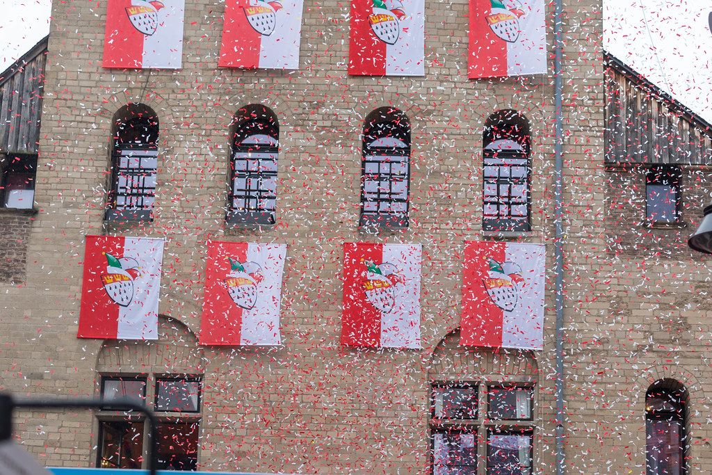 Red-white banners with the coat of arms of the city of Cologne hanging on the exterior of Severinstorburg, while the air is filled by red and white confetti during the Rose Monday parade