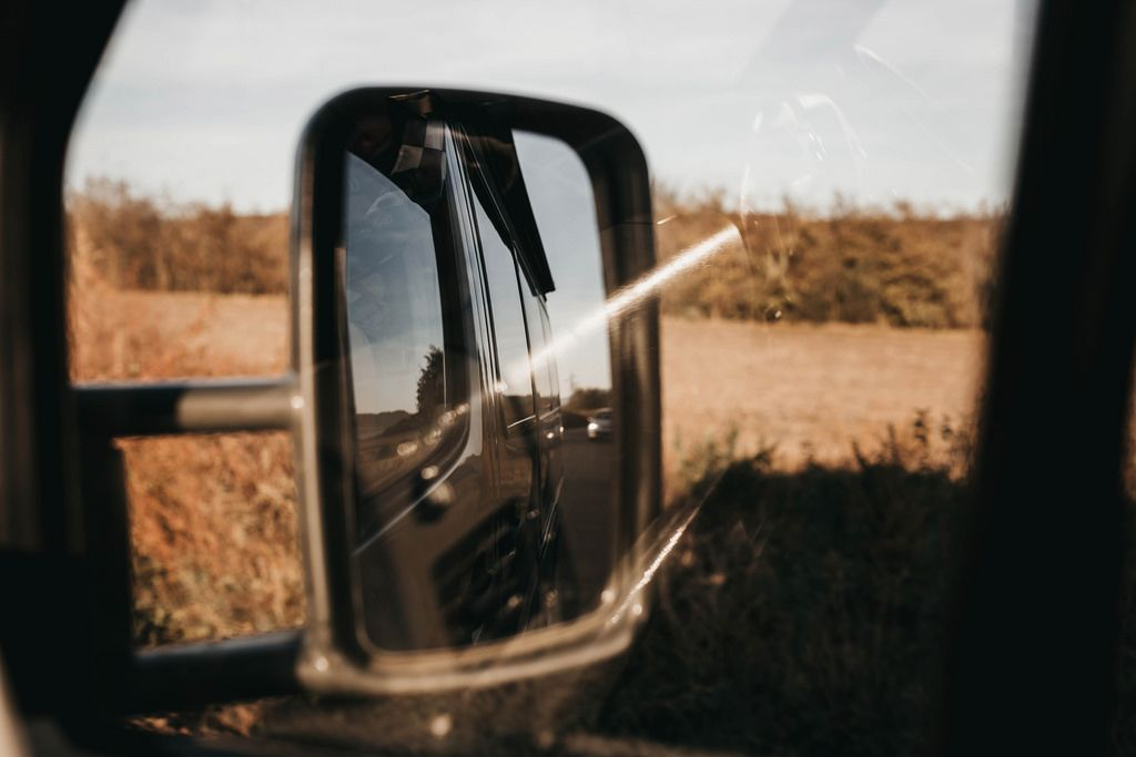 Reflection in the side mirror of bus. Road trip