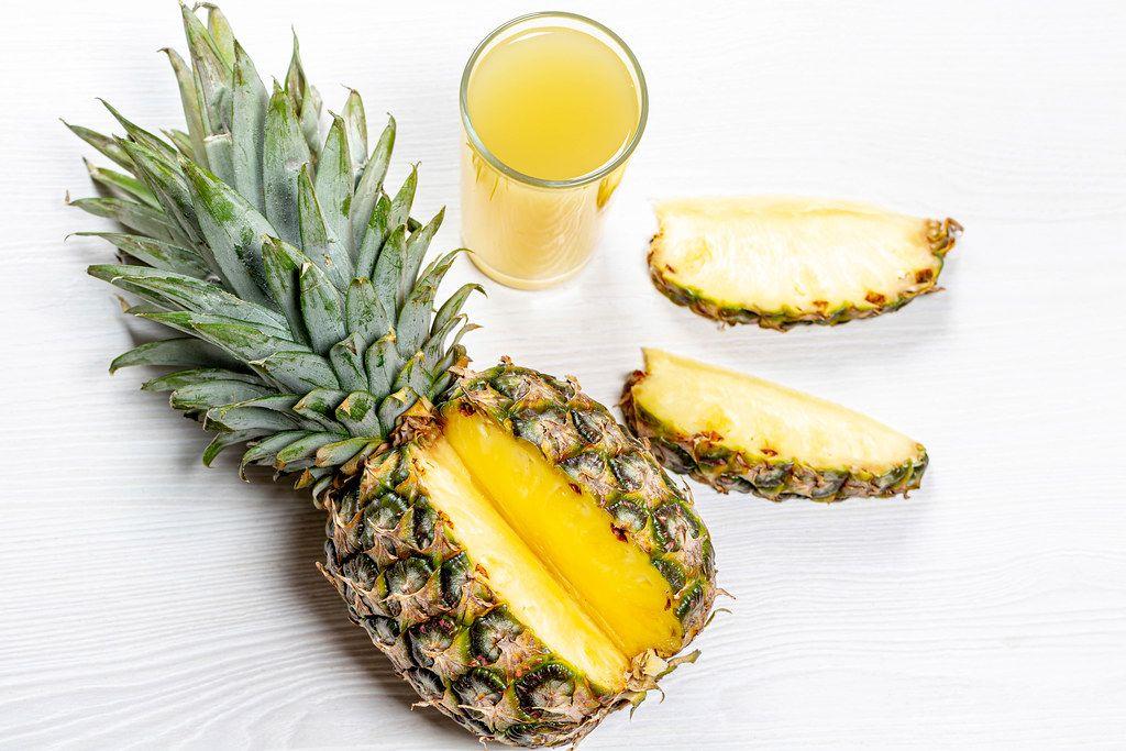 Reife Ananas aufgeschnitten neben einem Glas mit Ananassaft top-view