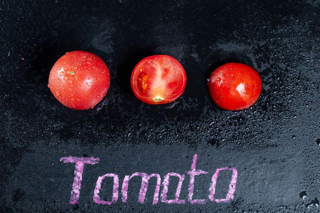 Reife Tomaten mit Wassertropfen auf schwarzem Hintergrund mit der Schrift Tomato