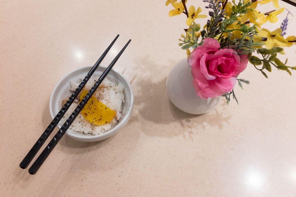 Reis in der Schüssel, Essstäbchen und Blumen in der Vase