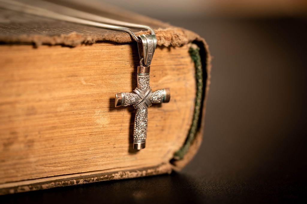 Religiöses Buch mit abgenutztem Einband und darübergelegter Halskette mit Kreuzanhänger