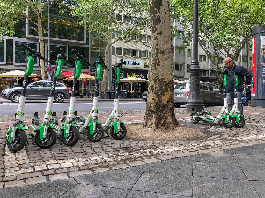 Rentable E-scooter by Lime at the roadside in Cologne to move car-free through the city