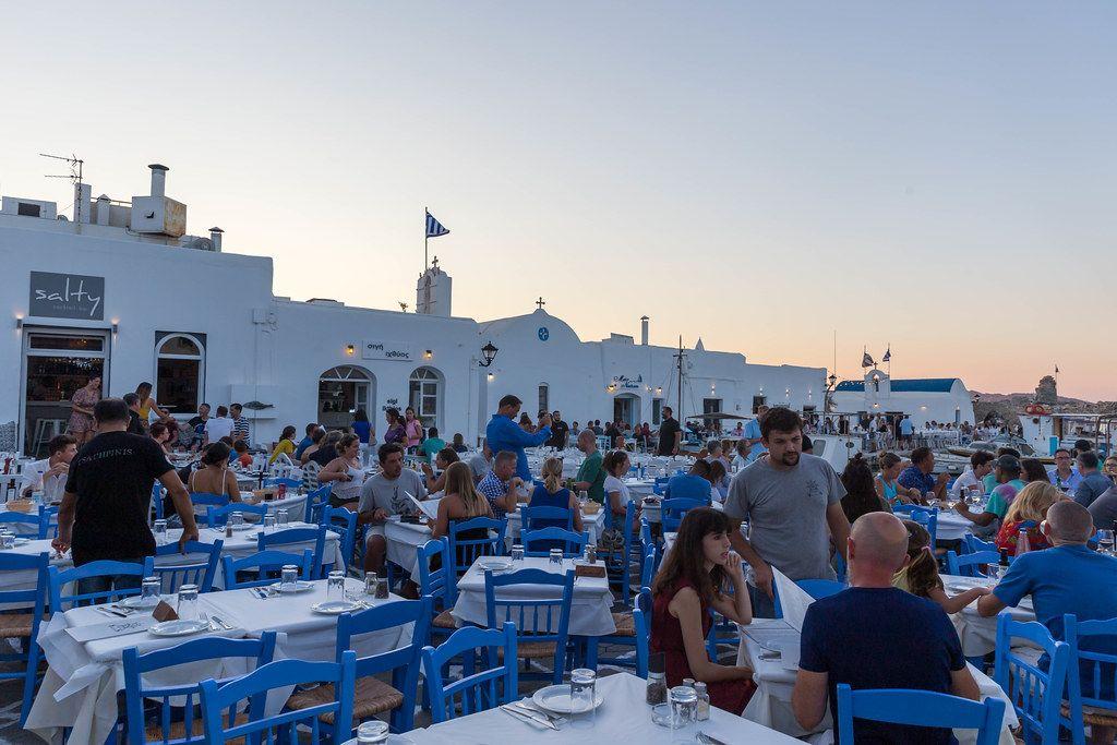 Restaurantgäste genießen Abendessen zum Sonnenuntergang an Hafen auf Paros, Griechenland