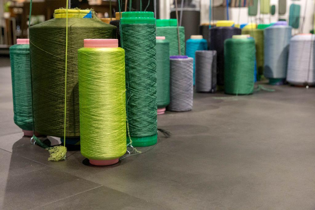 Riesige Spulen mit Faden in verschiedenen Farben stehen aufrecht auf Boden einer Fabrikhalle