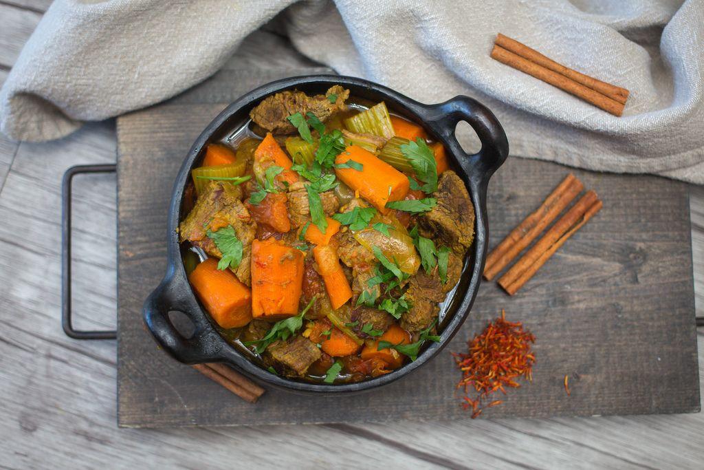 Rindfleisch-Tajine mit Karotten, Sellerie und Petersilie mit Zimtstangen und Safran auf Holzbrett