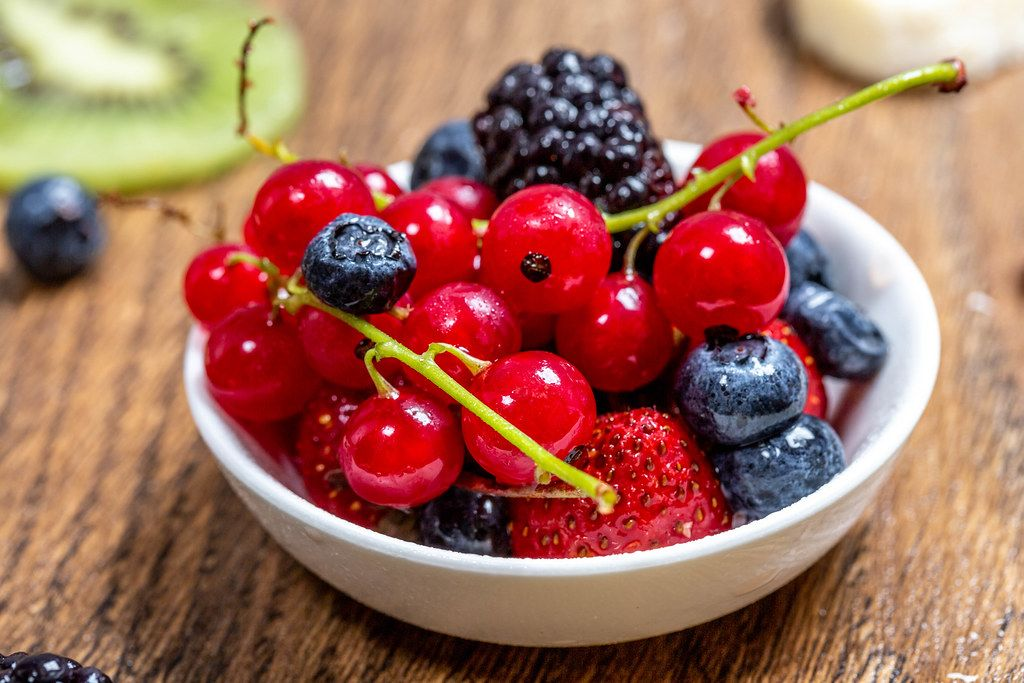 Ripe berries in a bowl on a wooden table (Flip 2019)