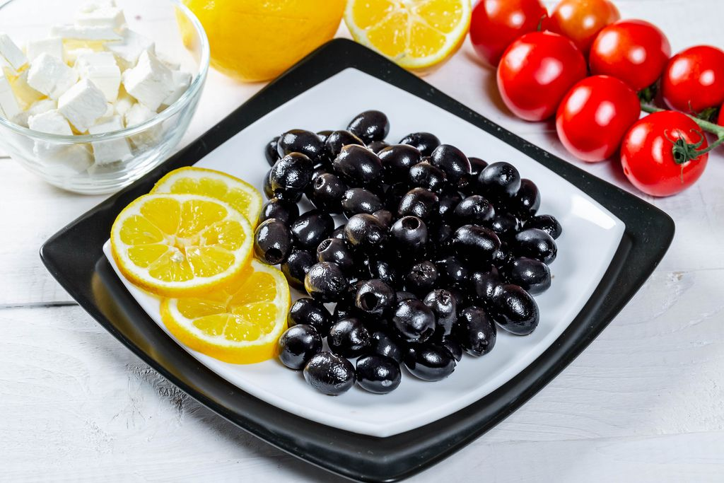 Ripe black olives with feta cheese, lemon and vegetables