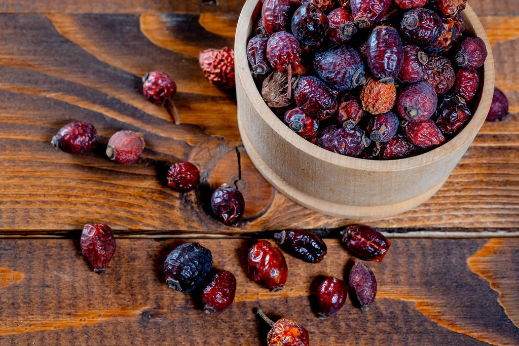 Ripe dried rosehip fruit in a bowl on wooden background