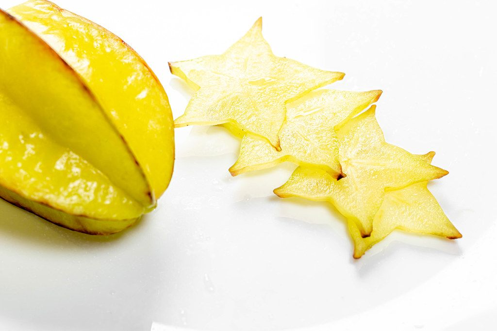 Ripe star fruit with slices on white background - carambola