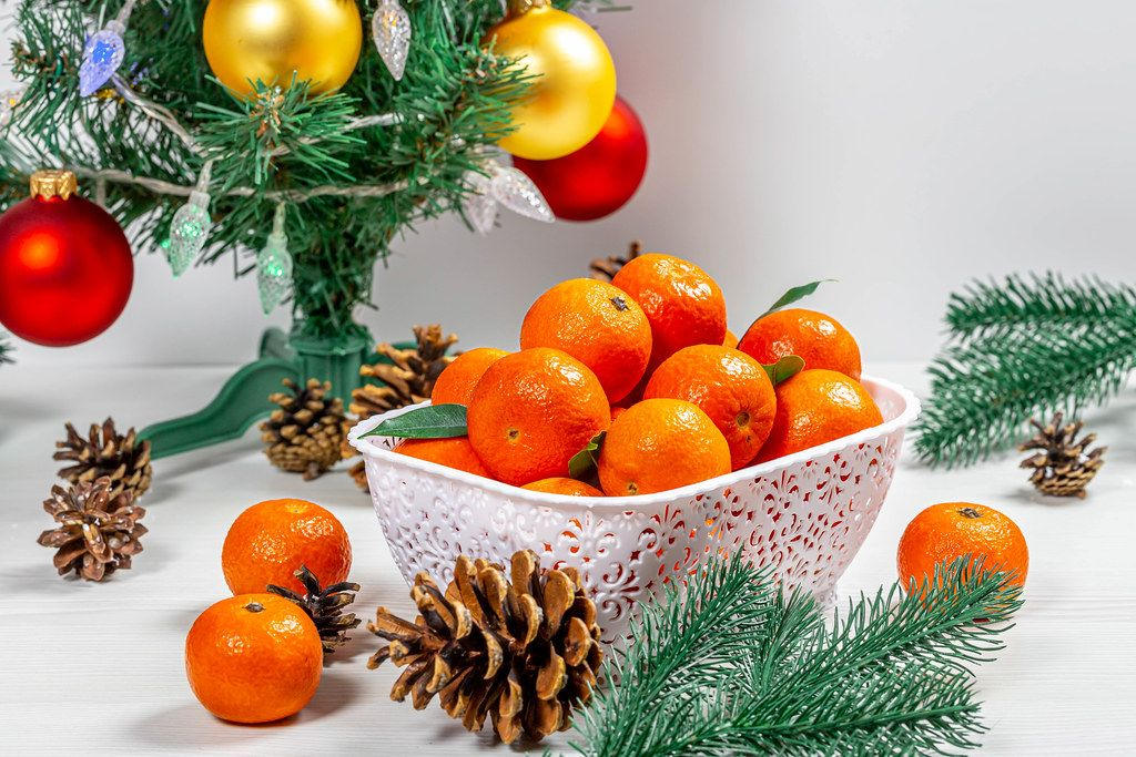 Ripe tangerines with cones and tree branches under a decorated Christmas tree (Flip 2019)