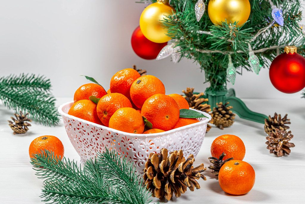 Ripe tangerines with cones and tree branches under a decorated Christmas tree