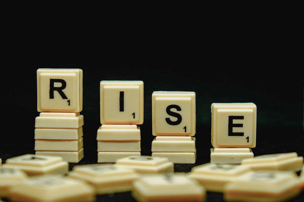 Rise word with scattered scrabble and black background
