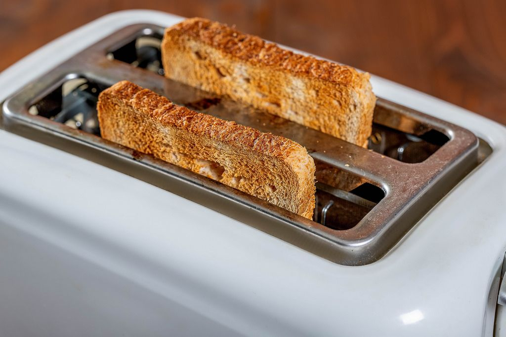 Roasted bread popping up from toaster machine